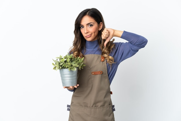 Gardener girl holding a plant isolated on white wall showing thumb down with negative expression