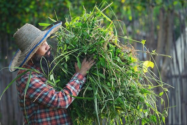 草の塊を腕に抱えている庭師