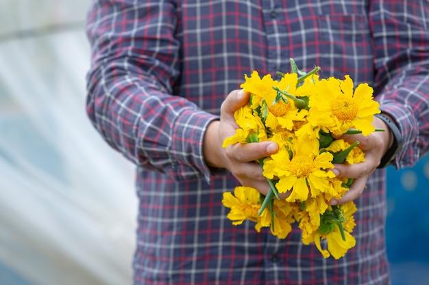 Giardiniere che tiene il fiore di calendula in campo