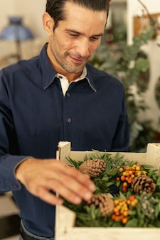 Gardener looking at floral wreaths medium shot