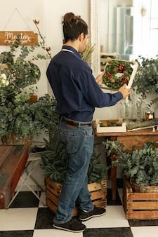 Gardener looking at floral wreaths