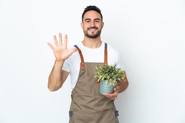 손가락으로 5 세 격리 된 흰색 배경 위에 식물을 들고 정원사 남자