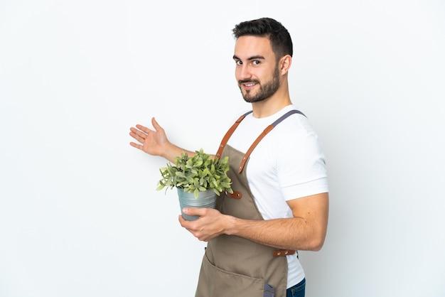 흰색 배경에 고립 된 식물을 들고 정원사 남자와 서 초대를 위해 손을 옆으로 확장