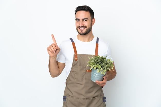 흰색 배경에 고립 된 식물을 들고 정원사 남자가 보여주는 최고의 기호에 손가락을 들어 올려