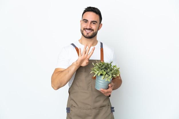 흰색 벽에 고립 된 식물을 들고 정원사 남자 행복하고 손가락으로 4 세