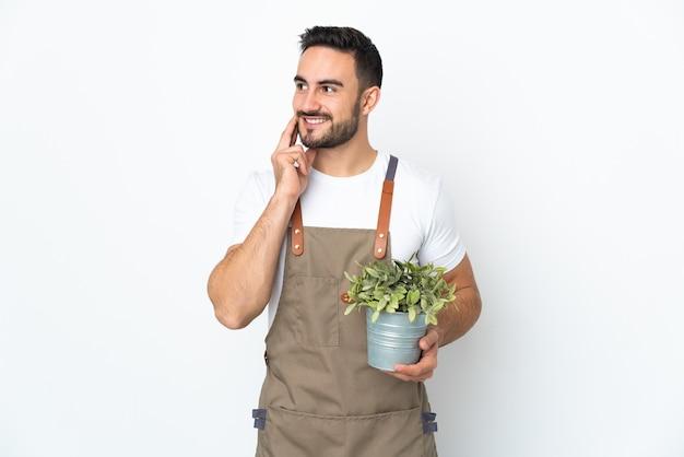 見上げながらアイデアを考えて白い壁に隔離された植物を保持している庭師の男