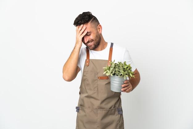 격리 된 흰색 배경 웃 고 위에 식물을 들고 정원사 남자