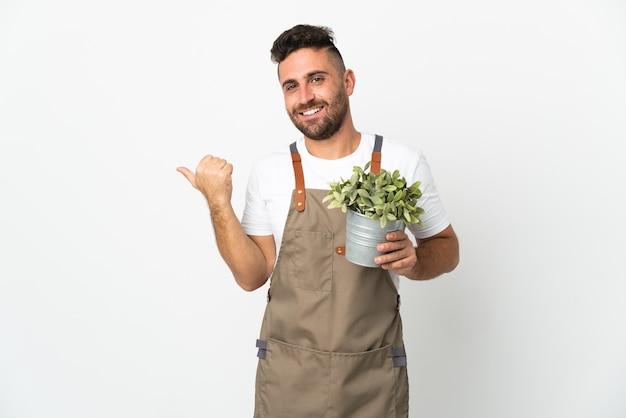 製品を提示する側を指している孤立した白い背景の上に植物を保持している庭師の男