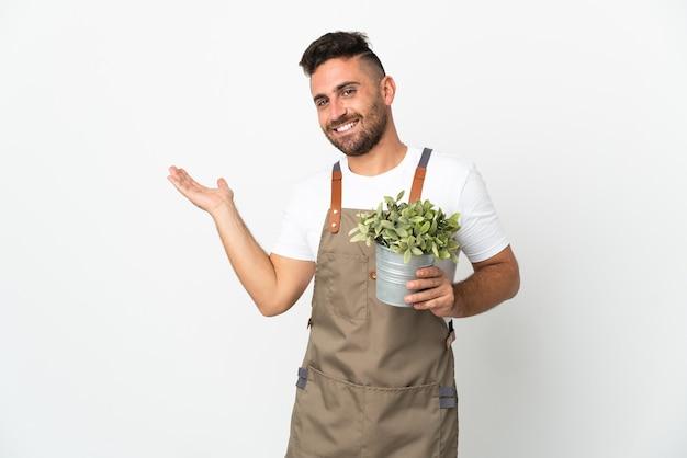 고립 된 흰색 위에 식물을 들고 정원사 남자와 서 초대하기 위해 손을 옆으로 확장