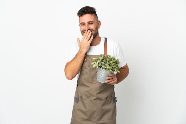 격리 된 흰색 위에 식물을 들고 정원사 남자 행복 하 고 손으로 입을 덮고 웃 고