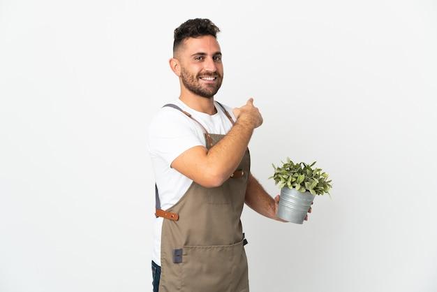 다시 가리키는 격리 된 흰색 위에 식물을 들고 정원사 남자