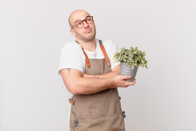 정원사 남자는 어깨를 으쓱하고, 혼란스럽고 불확실한 느낌을 받고, 팔짱을 끼고 의아해하는 표정으로 의심합니다.