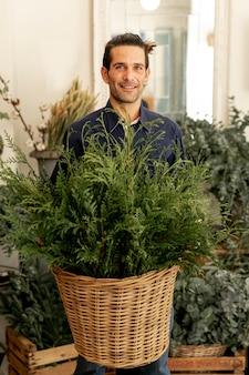 Садовник мужчина с длинными волосами держит корзину с листьями