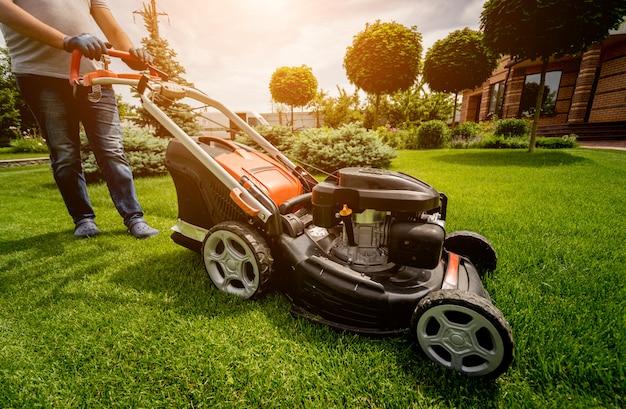 잔디를 깎고 정원사. 조경 설계. 녹색 배경