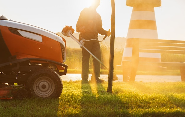 Gardener mows the lawn in the early morning at dawn. lawn care.