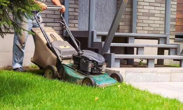 庭師は庭の緑の芝生を刈り取ります。