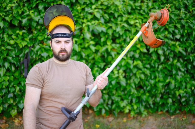 Gardener posing with grass trimmer on lawn in garden outdoors