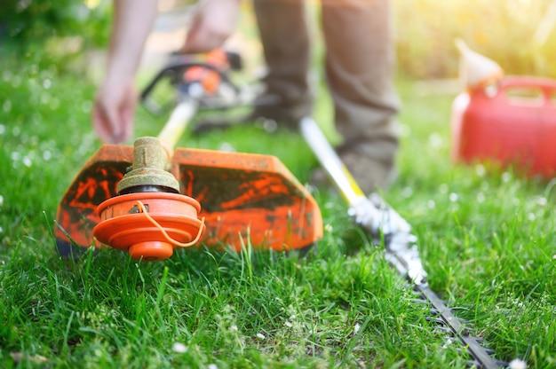 屋外の庭の芝生の上の草のトリマーを準備する庭師