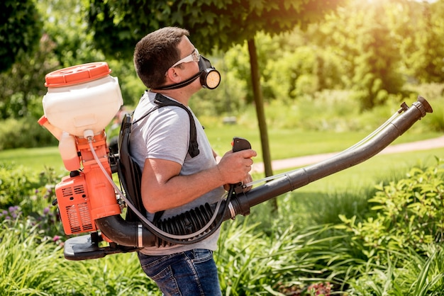 Gardener in protective mask and glasses spraying toxic pesticides trees and bushes. landscape design. gardening