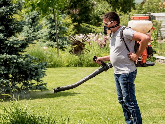 Gardener in protective mask and glasses spraying toxic pesticides trees