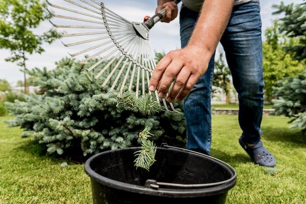 庭師は庭で葉を刈り取ります。