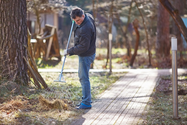 Gardener raking fall leaves in garden. copy space.