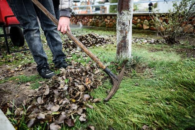 정원에서 단풍을 긁어 모으는 정원사