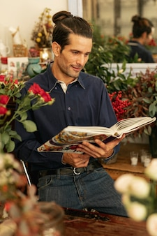 Gardener reading from a book and being surrounded by plants