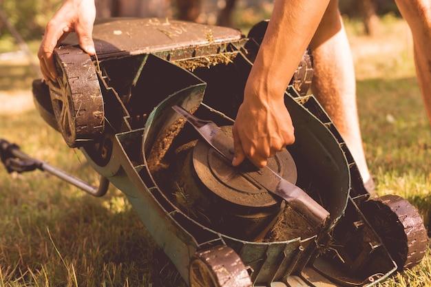 Садовник ремонтирует и ремонтирует газонокосилку в саду