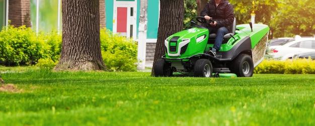 Садовник катается на газоне, подъезжает к трактору и косит лужайку с зеленой травой в парке.