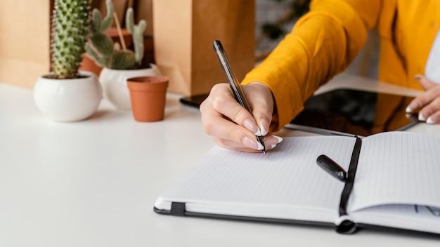 空白のノートにメモを取る庭師