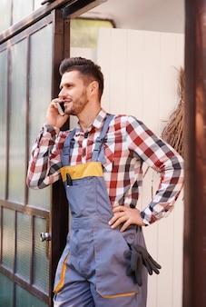 Садовник разговаривает по мобильному телефону