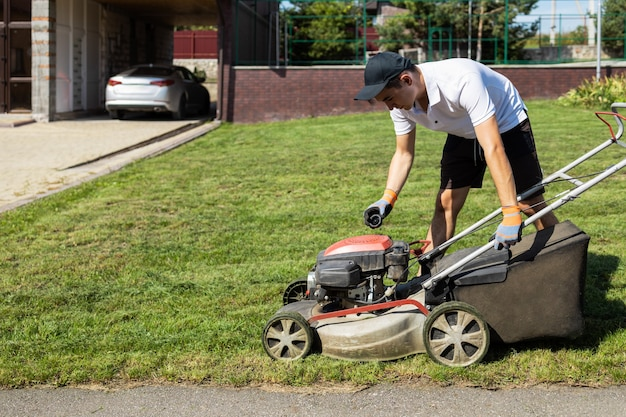 Gardener unscrews the gasoline cap of the lawn mower to fill the fuel tank