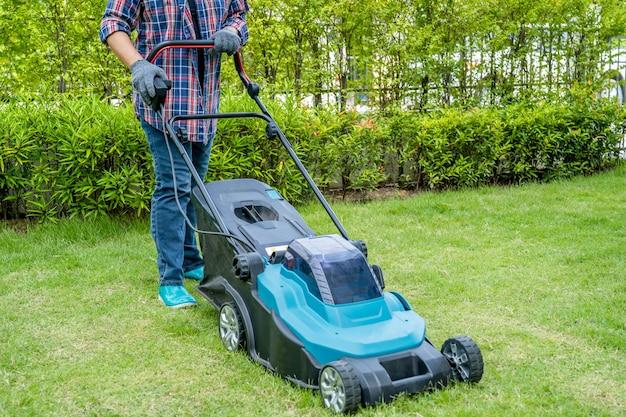 庭師は芝刈り機で緑の草を刈り、趣味で家の庭を植えます。