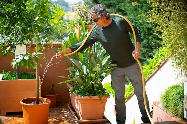 Gardener watering plants on a sunny day