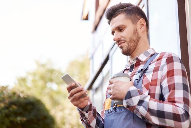 Садовник с кофе с помощью мобильного телефона