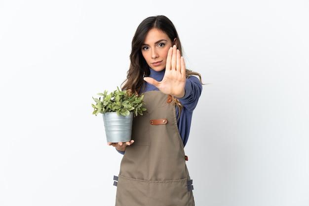 고립 된 식물을 들고 정원사 여자 중지 제스처를 만들기