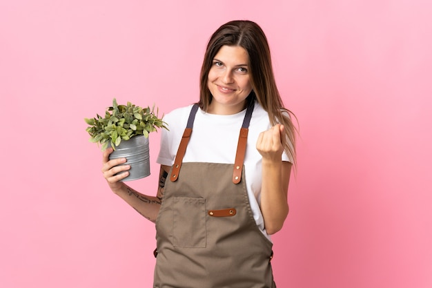 Gardener woman holding a plant isolated on pink  making money gesture