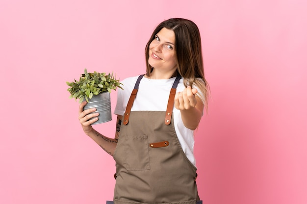 Gardener woman holding a plant isolated on pink wall making money gesture