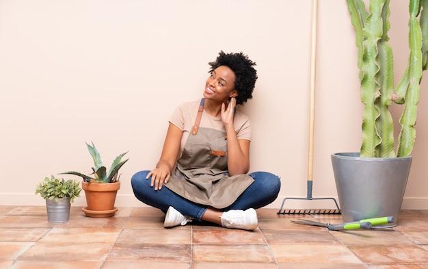 Gardener woman sitting on the floor among plants
