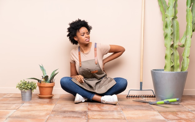 Gardener woman sitting on the floor around plants