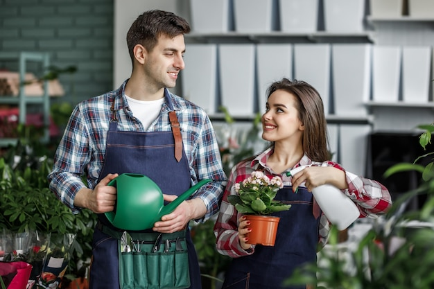 Gardeners couple, girl and man with plants in beautiful garden center or botanical center