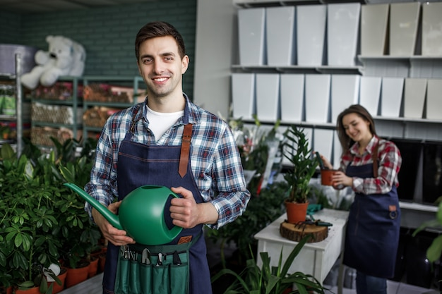 Gardeners happy boy and girl holding pots with plants in beautiful garden center