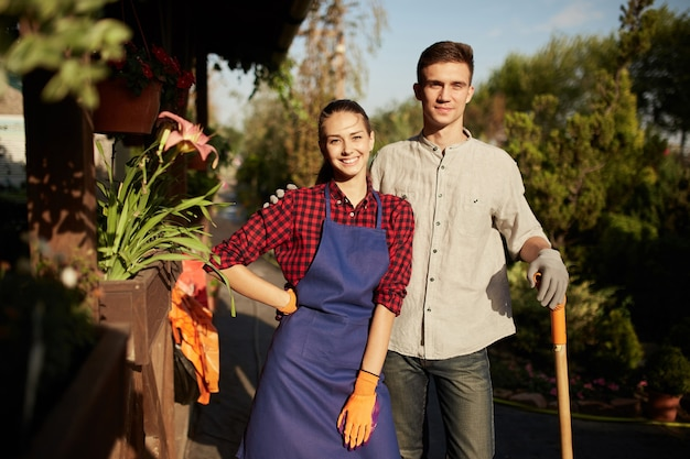 Садовники симпатичная девушка в фартуке и парень с лопатой стоит в чудесном саду в солнечный день.