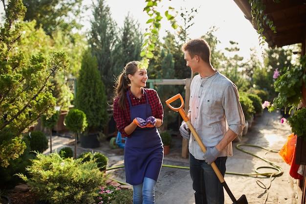 Садовники симпатичная девушка в фартуке и парень с лопатой гуляют по садовой дорожке в чудесном саду в солнечный день.