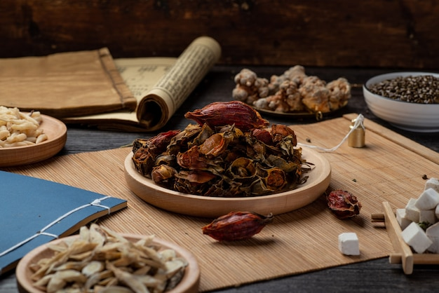 Gardeniaā古代漢方薬の本とテーブルの上のハーブ