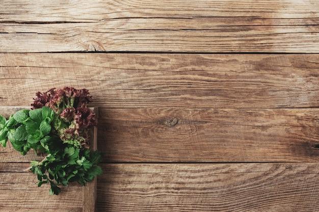 다른 허브와 샐러드와 원예 및 건강 한 먹는 개념 나무 용기에 나무 배경에 나뭇잎