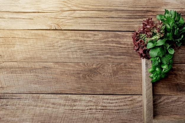 木製コンテナの木製の背景にさまざまなハーブとサラダの葉を使ったガーデニングと健康的な食事のコンセプト