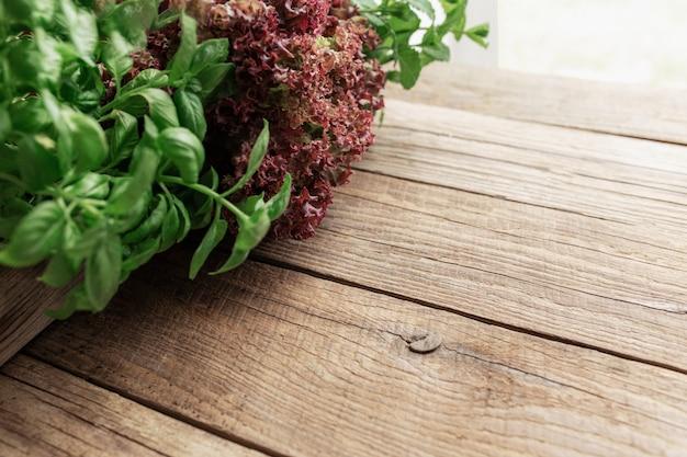 木製の背景にさまざまなハーブとサラダの葉を使ったガーデニングと健康的な食事のコンセプト