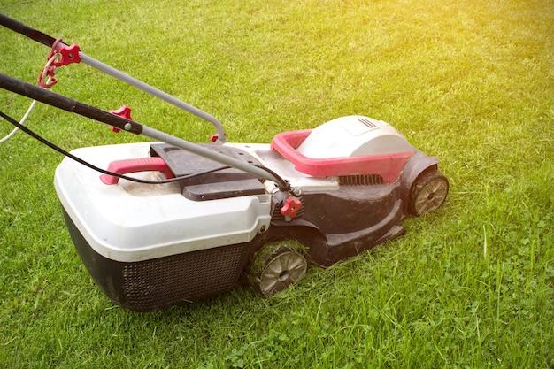 원예 및 조경 개념입니다. 잔디에 녹색 잔디 깎는 기계. 원 예 배경입니다.